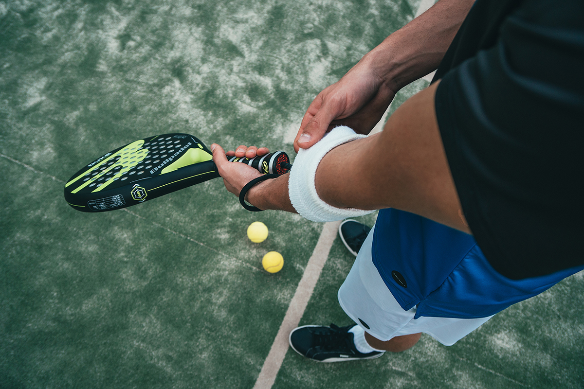person holding black and green tennis racket 1103829